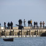 Class of February 2016 - Onlookers stand on the harbour wall and watch the boats sail out to sea